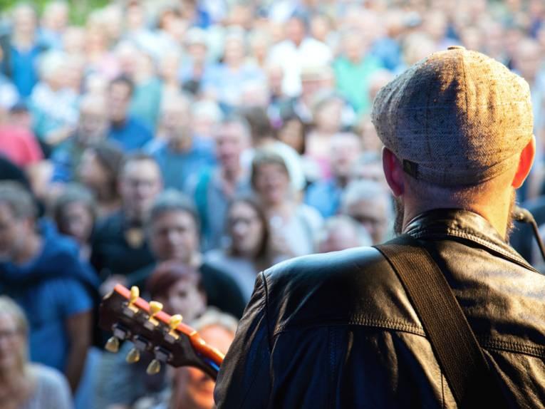 Blick von einer Bühne über die Schulter des Sängers und Gitarristen während eines Konzertes auf das Publkum.