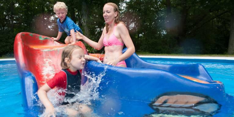 Frau mit zwei Kindern an einem Spielgerät, dass in einem Nichtschwimmerbereich eines Freibades steht