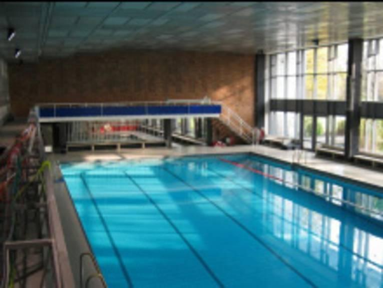 Innenraum einer Schwimmhalle: das Schwimmbecken und ein Teil der Fensterfront sind zu sehen