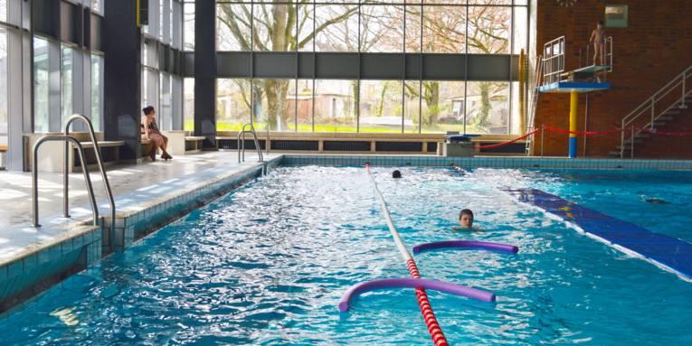 Schwimmbecken mit Schwimmern, Poolnudeln und Bahnbegrenzungen