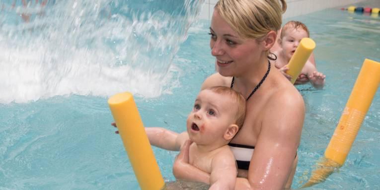 Mutter mit Baby im Hallenbad im Kinderbecken auf einer Poolnoodle
