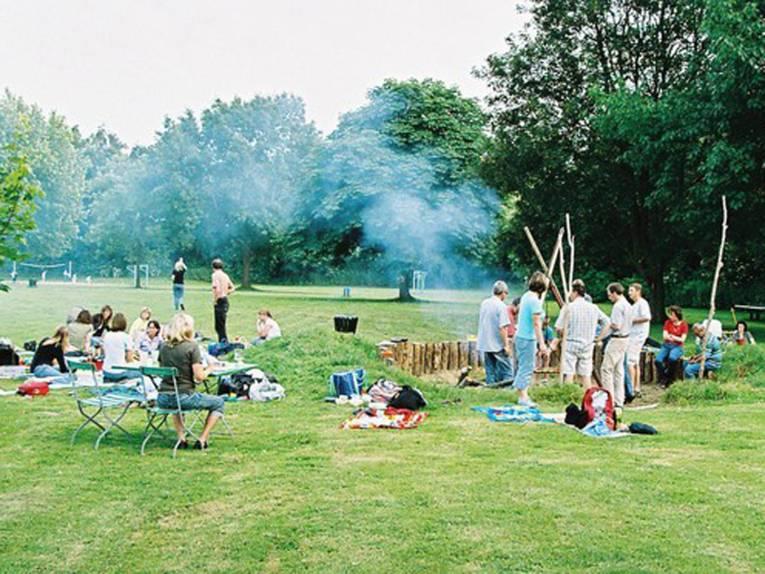 Auf einer Wiese picknickende Menschen, von denen sich ein Teil um ein Lagerfeuer gruppiert