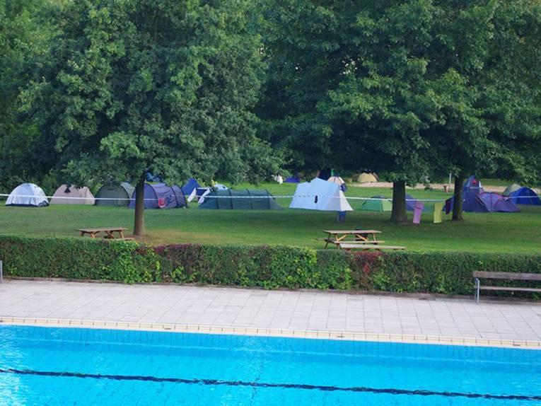 Zeltlager auf der einer mit Bäumen bestandenen Wiese, im Vordergrund Teile eines Schwimmbecken