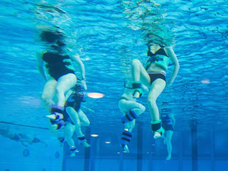 Unterwasseraufnahme von Menschen beim Aqufitnes mit Gewichtsmanschetten und Schwimmgürteln