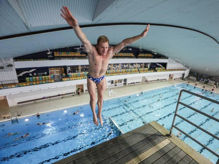 Ein Mann springt in einem Hallenbad vom Sprungturm