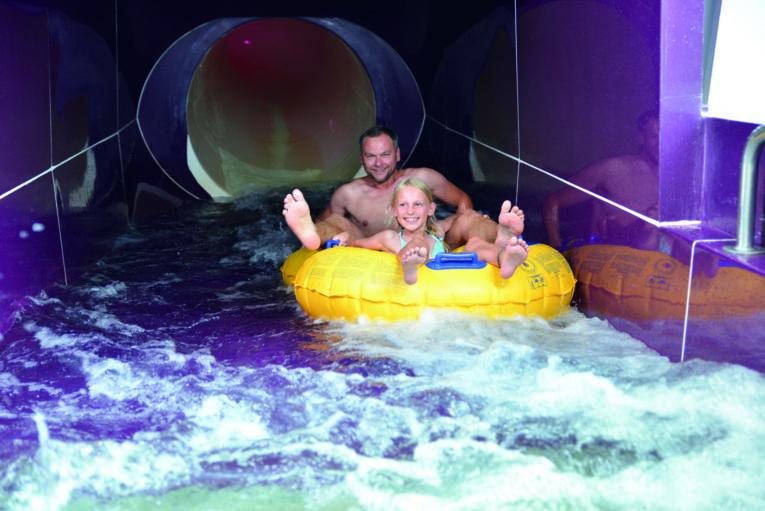 Zwei Personen in einem gelben Kunststoffreifen auf einer Wasserrutsche