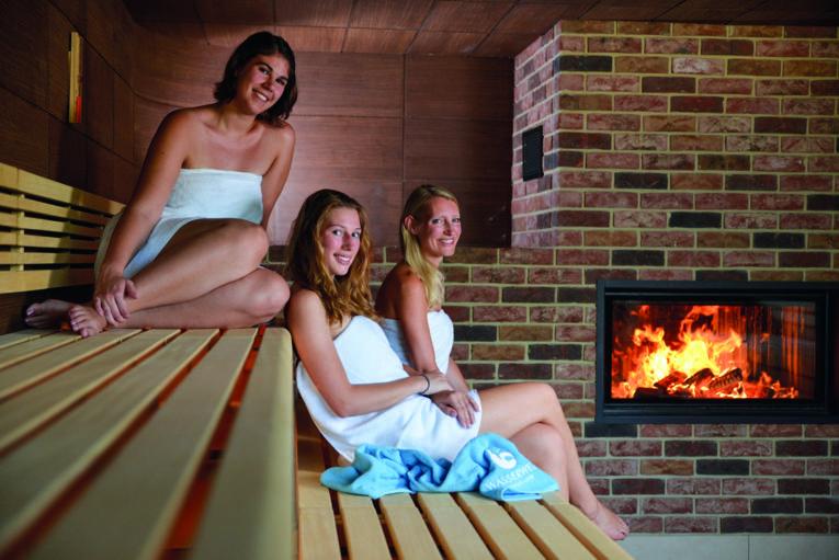 3 Frauen, in Badetücher gehüllt, auf Saunabänken, im Hintergrund ein Kaminofen mit loderndem Feuer
