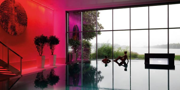 Blick über die Wasserfläche eines Schwimmbeckens, am hinteren Beckenrand sind zwei junge Frauen, dahinter ist eine große Fensterfläche. Durch die Fenster ist der Maschsee zu sehen.