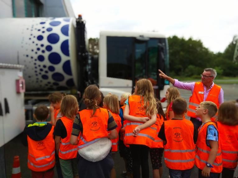 Eine Gruppe von Kindern mit Warnwesten vor einem Müllwagen und einem Mann, der ihnen etwas erklärt