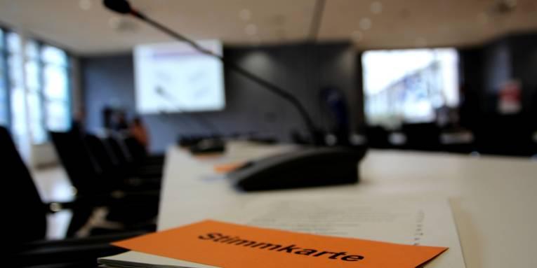 Eine orangefarbene Stimmkarte liegt in einem Sitzungsraum auf einem Tisch. Im Hintergrund ein Tischmikrophon, Stühle und eine Leinwand mit Präsentation.