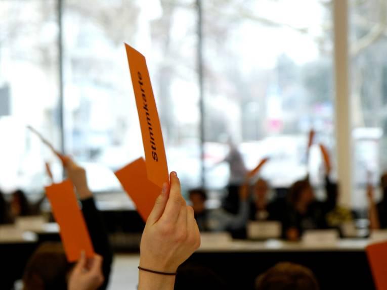 Im Vordergrund hält eine Hand eine orangefarbene Stimmkarte in die Höhe. Verschwommen sind im Hintergrund weitere solcher Karten und an Tischen sitzende Menschen zu sehen.
