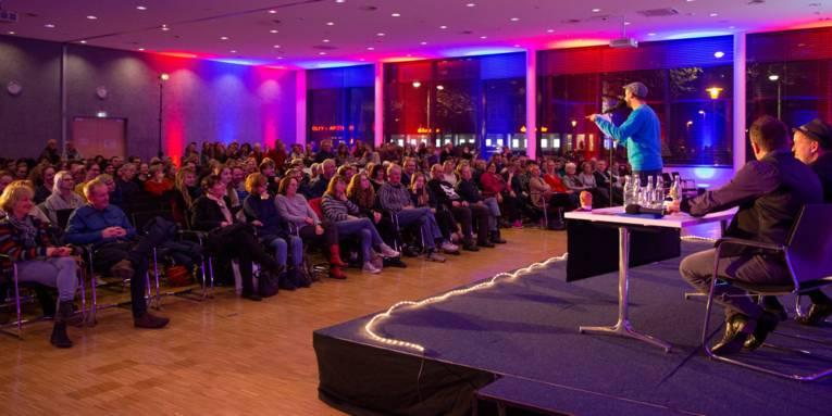 Ein bunt beleuchteter großer Raum mit Publikum in Sitzreihen und einer Bühne