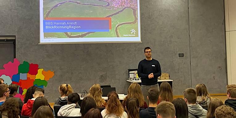 Schülerinnen und Schüler in einem Sitzungssaal schauen eine Präsentation an. Eine junger Mann erklärt etwas dazu.