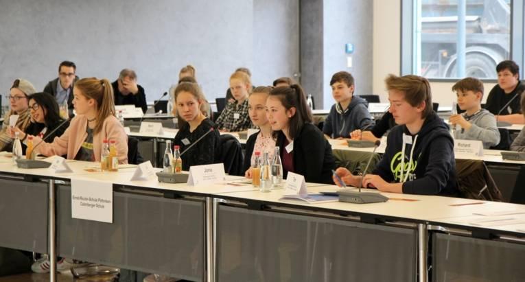 Mehrere Schülerinnen und Schüler sitzen an Tischreihen.