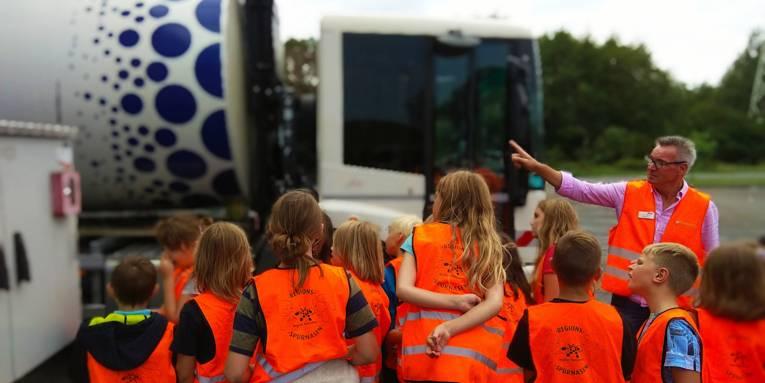 Kinder mit leuchtenden Warnwesten vor einem Müllwagen, ein Mann erklärt etwas.