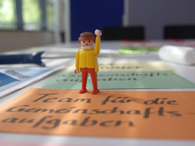 Eine Playmobil-Figur steht auf einem Tisch mit bunten Moderationskarten