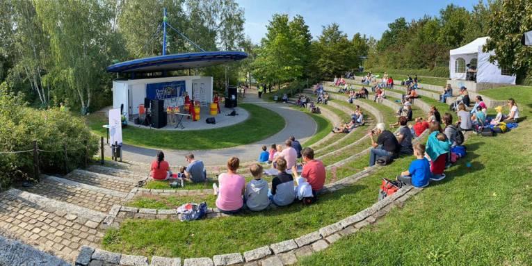 Menschen sitzen mit Abstand in einem Rondell und verfolgen das Programm auf einer Bühne.