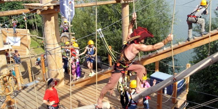 Mehrere Personen klettern an Seilen, im Vordergrund klettert ein Betreuer, der wie ein Pirat verkleidet ist.