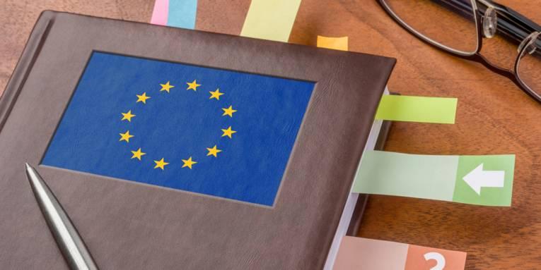 Geschäftsbuch mit der Flagge der EU und Post-its