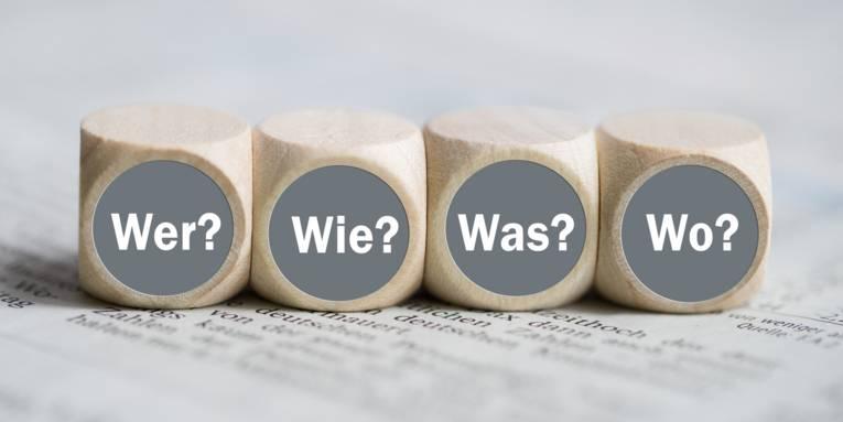 """Würfel mit den Wörtern """"Wer, Wie, Was und Wo"""" auf einer Zeitung"""