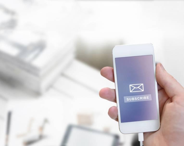 """Eine Hand hält ein weißes Smartphone mit blauem Bildschirmhintergrund auf dem ein Briefumschlag und das Wort """"subscribe"""" zu sehen ist."""