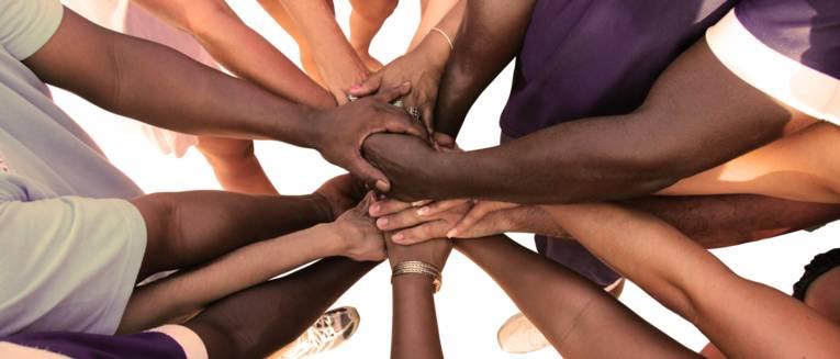 Die Arme einer Gruppe von vielfältigen Menschen bildet eine Einheit.