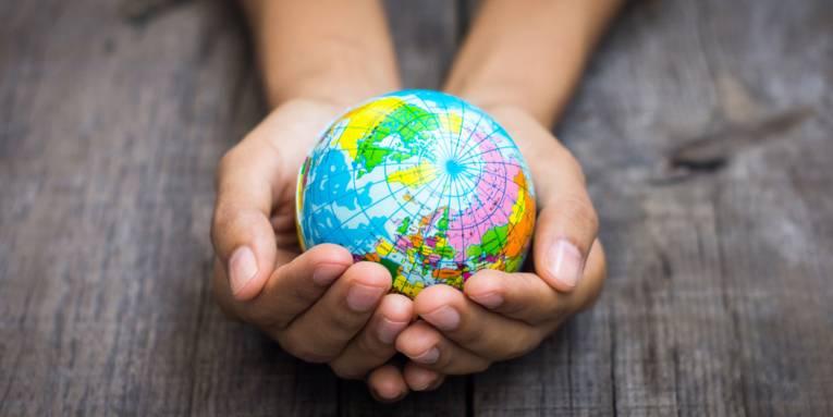 Person hält eine kleine Weltkugel in der Hand