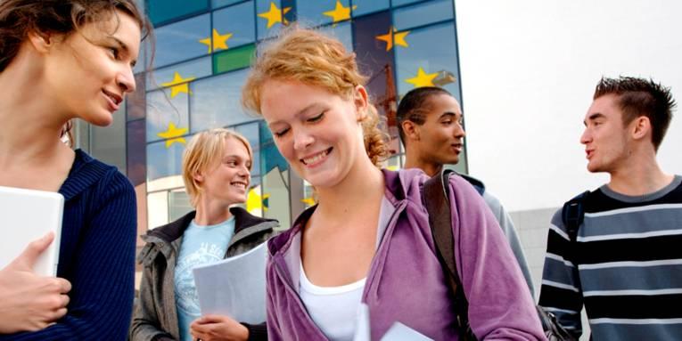 Jugendliche mit Unterlagen vor einem Gebäude mit den Sternen der EU