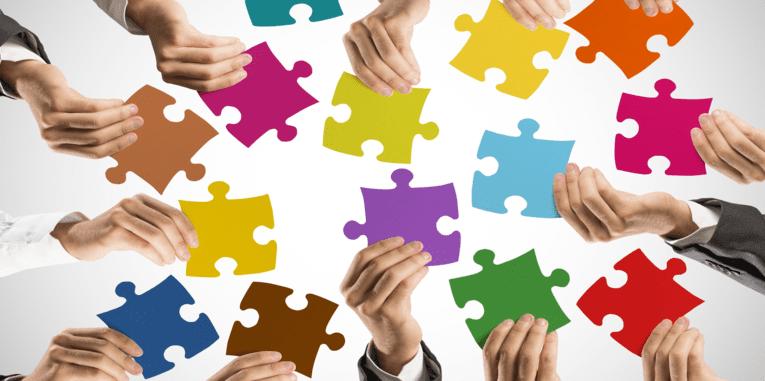 Mehrere Hände halten bunte Puzzleteile