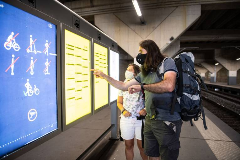 Passengers with face masks looking at the train schedule