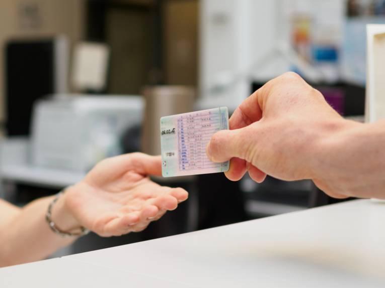 Eine Hand übergibt einen Führerschein in eine andere Hand