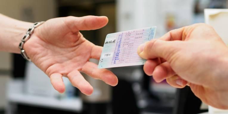 Ein Führerschein wird von einer Hand in eine andere übergeben.Änderung des Führerscheins.