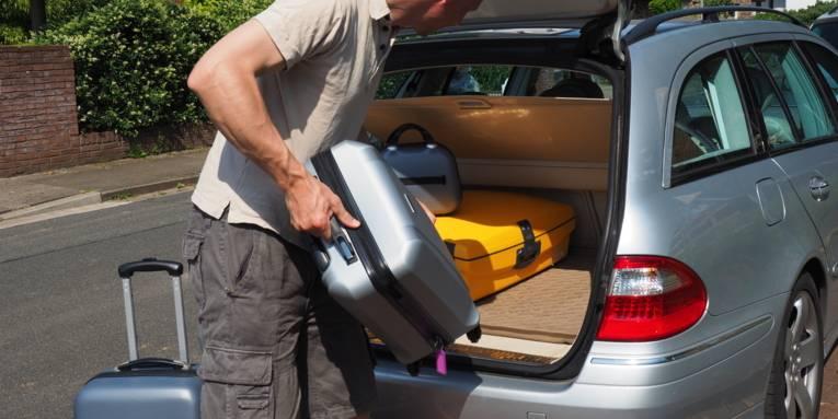 Ein Mann belädt seinen Kofferraum mit Reisegepäck.