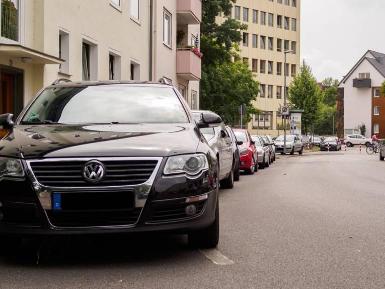 Eine Straße in einer Wohngegend mit parkenden Autos am Rand.