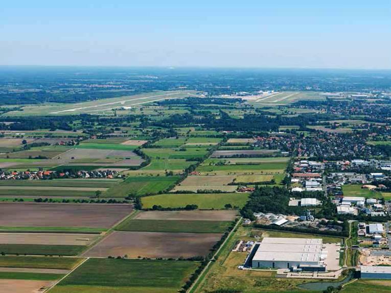 Blick über eine große Flächen mit grünen Flächen, Feldern und Industriegebieten.