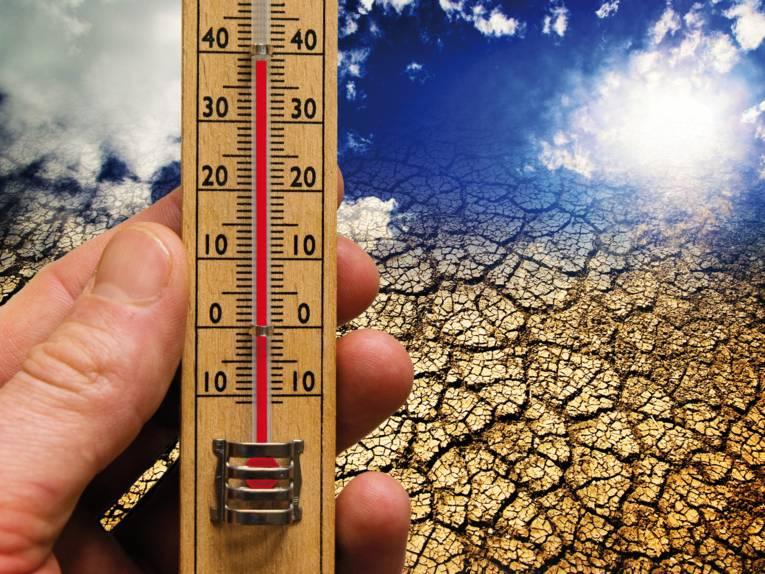 Hand mit einem Thermometer. Im Hintergrund befindet sich eine Dürre-Zone.