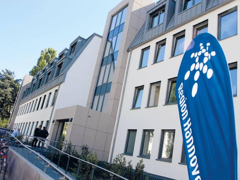 """Ein modernes Gebäude mit einer Rampe für einen barrierefreien Zugang. Im Eingangsbereich stehen zwei Personen und eine weitere Person schließt ihr Fahrrad an. Vorne rechts im Bild ist ein blauer Aufsteller mit der Aufschrift """"Region Hannover"""" zu sehen (das Wort Hannover ist zum Teil abgeschnitten)."""