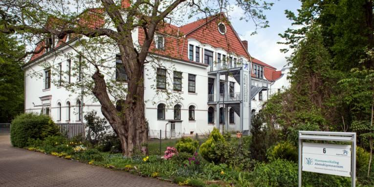 Gebäude mit weißer Fassade und rotem Ziegeldach.