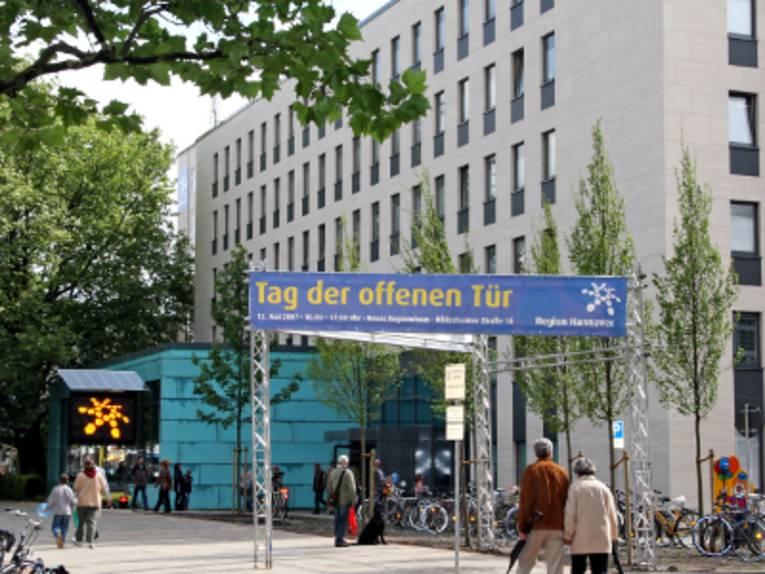 """Blick auf das Regionshaus, Eingang zur Foyer Hildesheimer Straße 18. Ein großes Banner weist auf die Veranstaltung """"Tag der offenen Tür"""" hin, verschiedene Aktionen und Attraktionen sind aufgebaut."""