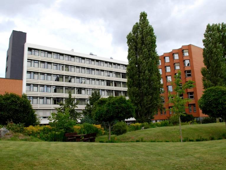 Gebäudekomplex in L-Form, der linke Teil ist weiß, der rechte, abgewinkelte Teil besteht aus roten Backsteinen. Vor dem Gebäude ist eine parkähnliche Fläche mit Rasen, Bäumen und Sträuchern zu erkennen.