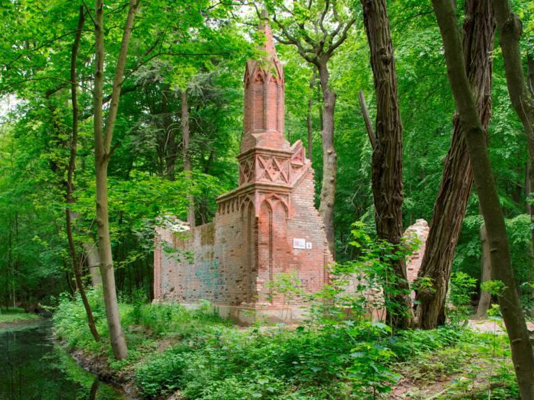 Die Ruine des Mausoleums, umgeben von Bäumen.
