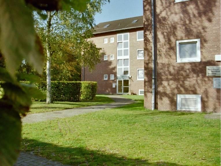 """Blick über eine Rasenfläche auf einen Backsteinbau, daran ist ein Schild mit der Aufschrift """"Pestalozzi Seminar""""."""