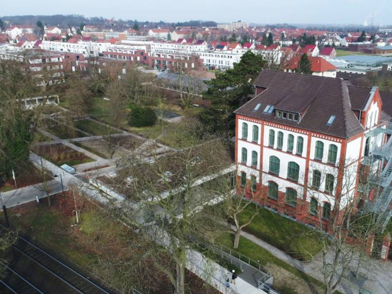 Ein Gebäude und das dazugehörige Gelände (inklusive Garten) von oben fotografiert.