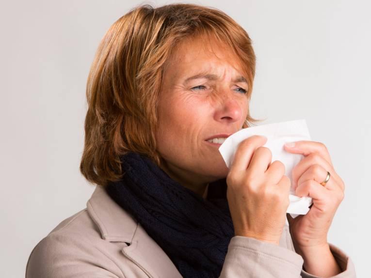 Eine Fra, die in ein Papiertaschentuch niest