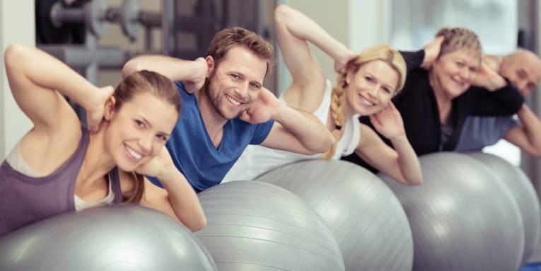 Eine Gruppe von Personen unterschiedlicher Altersgruppen trainiert in einem Fitnessraum mit großen Gymnastikball