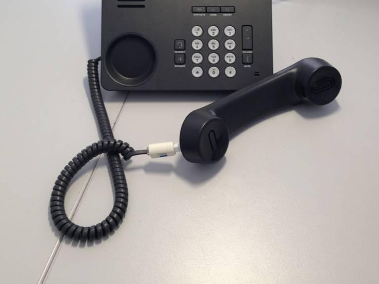 Ein schwarzes Telefon mit Tastatur, bei dem der Hörer abgenommen wurde und davor liegt.