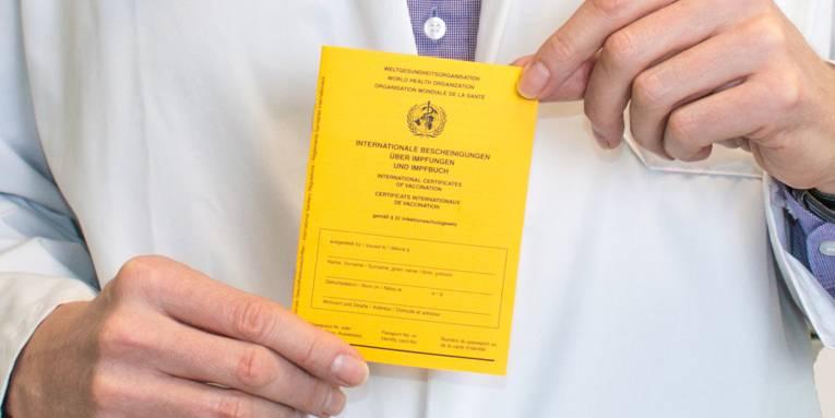 Eine Person im weißen Kittel hält ein Impfbuch in der Hand