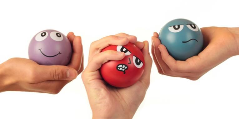 Drei Bälle mit aufgemalten Gesichtern, die die Stimmungslagen Zufrieden, Verärgert und Neutral, zeigen. Jeder Ball wird von einer Hand gehalten