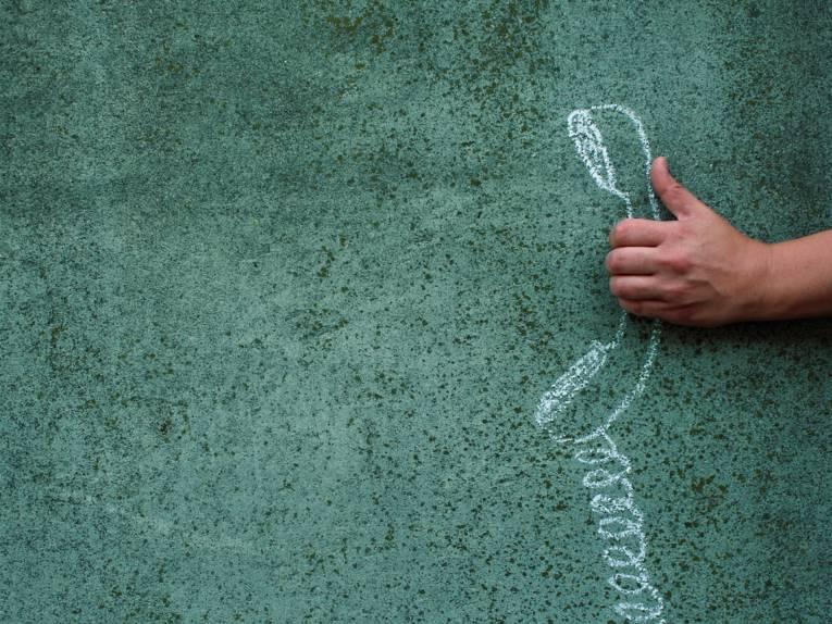 Hand greift ein an die Wand gemalten Telefonhörer.