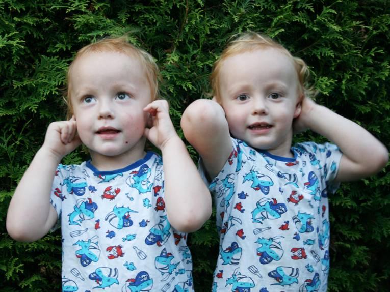 Zwei Kleinkinder im Porträt, beide gucken fröhlich und halten sich die Ohren zu.